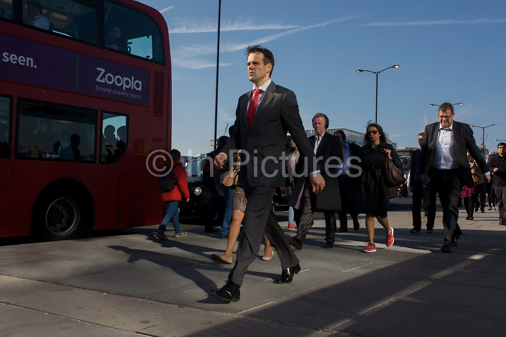 Londoners cross southbound over London Bridge during the evening rush hour. A smartly-dressed businessman walks briskly along with others commuters striding out of the City of London. There has been a crossing over the Thames here since the Romans first forded the river in the early 1st Century with subsequent medieval and Victorian stone bridges becoming an important thoroughfare from the City on the north bank, to Southwark on the south where transport hubs such as the mainline station gets commuters to the suburbs and satellite towns.