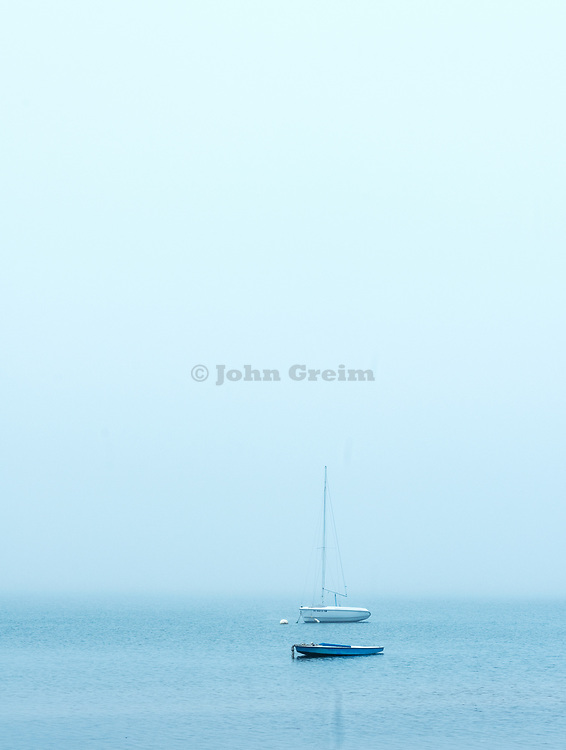 Boats in Pleasant Bay on overcast morning, North Chatham, Cape Cod, Massachusetts, USA.