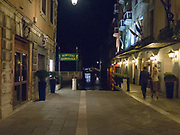 Couple walking past a gondola station at night in Venice