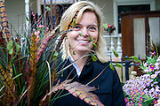 Happy woman enjoying a display of feathered floral arrangements. Grand Old Day Festival. St Paul Minnesota MN USA
