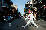 A man pretends to walk across the street behind a stuffed dog on a street in New Orleans, Louisiana.