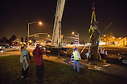 Workers lift the 12-foot Milpitas Minute Man sculpture into place with a crane, outside Milpitas City Hall in Milpitas, California, on January 24, 2014. (Stan Olszewski/SOSKIphoto)