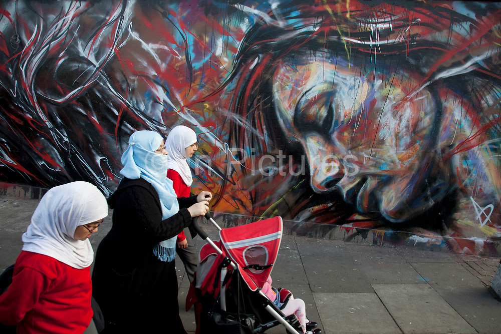 Muslim family walk past a wall by David Walker on Brick Lane. Street art in the East End of London is an ever changing visual enigma, as the artworks constantly change, as councils clean some walls or new works go up in place of others. While some consider this vandalism or graffiti, these artworks are very popular among local people and visitors alike, as a sense of poignancy remains in the work, many of which have subtle messages.