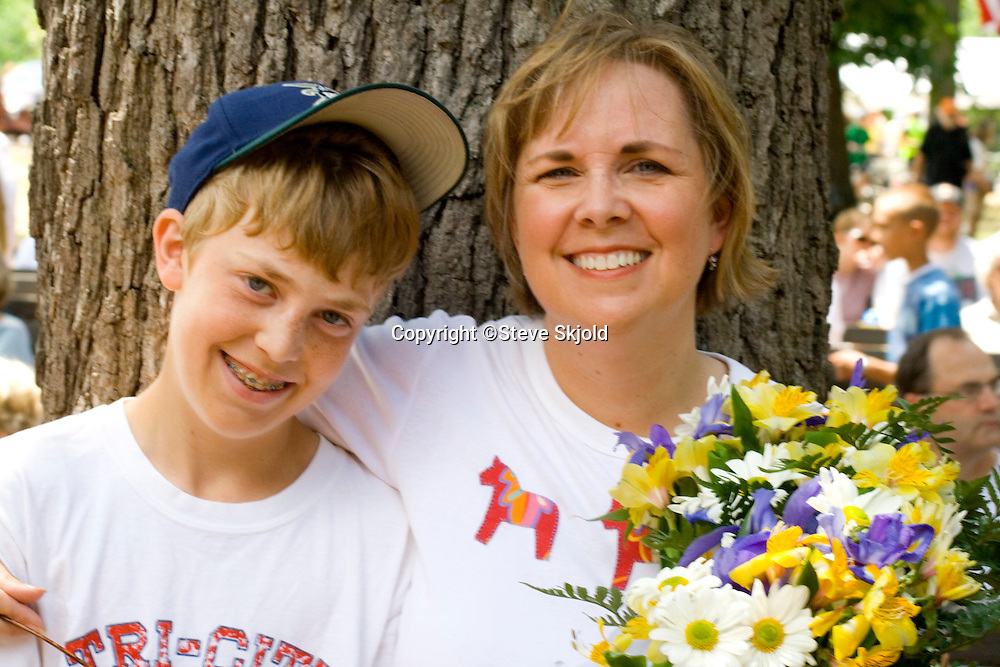 Mom holding bouquet and son enjoy festivities. Svenskarnas Dag Swedish Heritage Day Minnehaha Park Minneapolis Minnesota USA