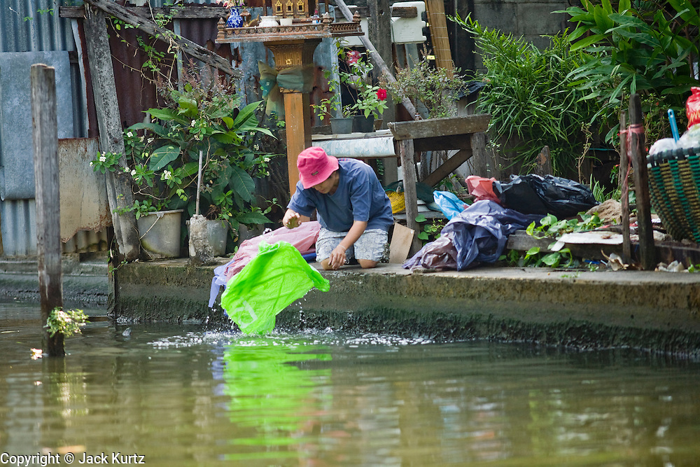 """02 MARCH 2008 -- BANGKOK, THAILAND:  A man does his laundry in a """"khlong"""" or canal in the Thonburi section of Bangkok, Thailand. Photo by Jack Kurtz/ZUMA Press"""