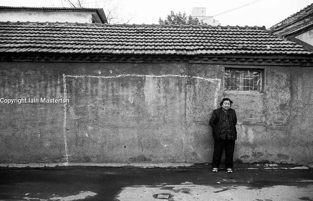Woman standing next to goals chalked on wall in hutong in Beijing China