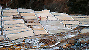 """Since pre-Inca times, salt farmers at the saltworks (salinas) near Maras have evaporated salty water from a subterranean stream in Peru, South America. A rough dirt road connects Maras (in the Urubamba/Vilcanota River Valley, Sacred Valley of the Incas) with Cuzco (40 km north) and other towns. The cooperative system of pond farmers was established during the time of the Incas, if not earlier, and is traditionally available to any person wishing to harvest salt. Intricate channels redirect water flow through several hundred ancient terraced ponds. As water evaporates from the sun-warmed ponds, it becomes supersaturated and salt precipitates as crystals. A pond keeper closes the water-feeder notch, allows the pond to go dry, then scrapes and carries away the dry salt. Salt color varies from white to a light reddish or brownish tan, depending on """"farmer"""" skills. Cropped from a 35mm film slide, 2003. Published in """"Light Travel: Photography on the Go"""" book by Tom Dempsey 2009, 2010."""