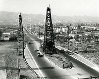1930 Looking north at oil derricks on La Cienega Blvd. at Third St.