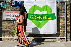 © Licensed to London News Pictures. 26/08/2019. London, UK. Two women walk past the Grenfell sign during the 2019 Notting Hill Carnival, Europe's largest street party and a celebration of Caribbean traditions and the capital's cultural diversity. Photo credit: Dinendra Haria/LNP