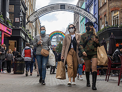 Licensed to London News Pictures. 22/10/2021. London, UK. Early Christmas shoppers wear masks on Carnaby Street, London today as Sage urges the government to be ready for a rapid deployment of stricter Covid measures if cases rise too quickly this winter. This week, Health Secretary Sajid Javid predicted new infections could rise to 100,000 a day this winter and urged eligible members of the public to get their booster jabs as soon as possible. Photo credit: Alex Lentati/LNP