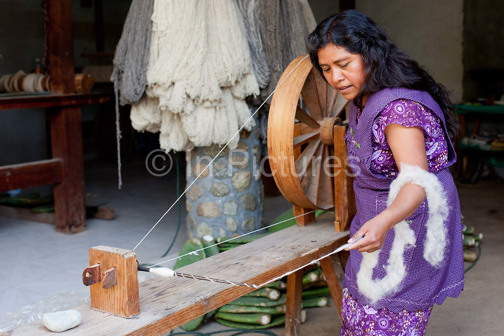 A female weaver spins yarn on a hand operated wheel in the traditional way. Oaxaca in southern Mexico is known for its artisan communities, with each valley having a different specialism - weaving, pottery, wood carving.