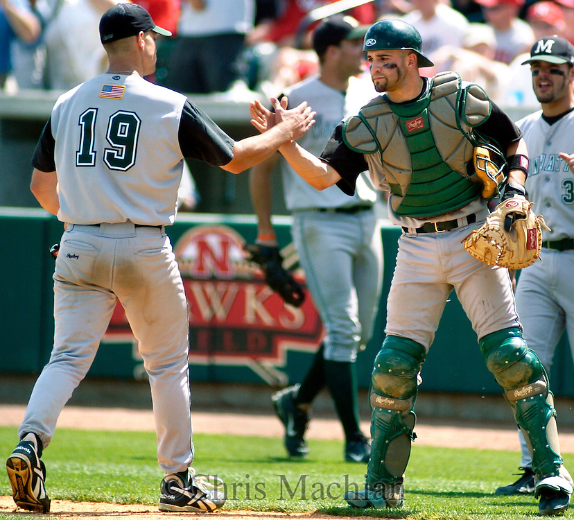 6/2/06 Lincoln, NE Manhattan University catcher Nick Derba greets pitcher Chris Cody at Haymarket Park in Lincoln Ne Friday afternoon.  Cody had just ended the 8th inning with a strikeout. (Chris Machian/Prairie Pixel Group)