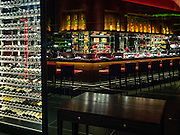 29 JANUARY 2016 - BANGKOK, THAILAND: The wine cellar (left) and dining counter (reflected in a mirrored wall) at L'atelier de Joel Robuchon, an exclusive French restaurant owned by French chef Joel Robuchon. The restaurant features counter style seating which looks into the kitchen so diners can watch the chefs work.          PHOTO BY JACK KURTZ
