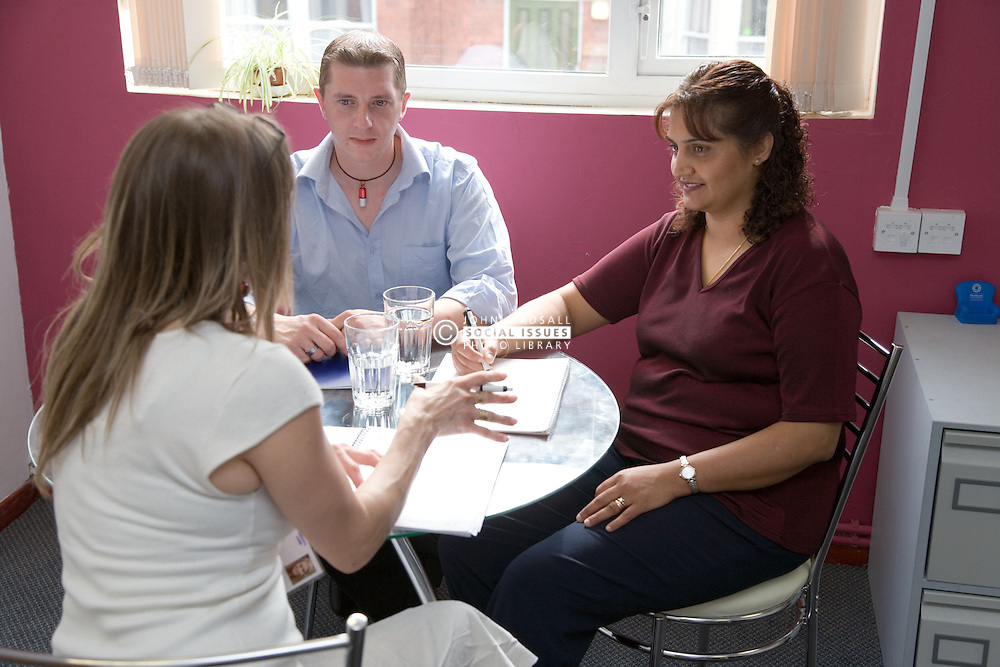 Three adults sitting round a table having a discussion,