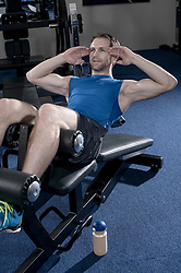 Mid adult man going sit-ups on bench for trains his abdominal muscles, Bavaria, Germany