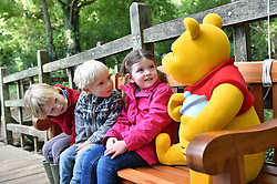 EDITORIAL USE ONLY<br /> (Left to right) Ed Clayton, three, Jacob O'Dell, four and Hetti Arnett, four, sit on a bench, known as a ÔThotful SpotÕ, that talks to you when you sit on it, at '100 Acre Woods' in Ashdown Forest, to celebrate the 90th anniversary of the publication of AA Milne's first collection of stories about Winnie-the-Pooh this Friday.