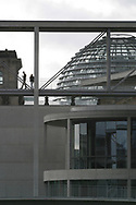 Figures cross a bridge above the Spree river, the line of the former Cold War barrier which was opened 15 years ago on 9th November 1989. This area behind the Reichstag (parliament) has been redeveloped and has become home to civil servants and other officials since the German government was moved from Bonn to Berlin.