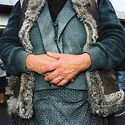 A woman wearing a fur-edged sheepskin waistcoat at Bogdan Voda market, Maramures, Romania