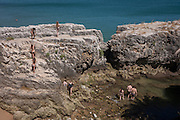 Aerial view of beachcombers as they explore rocks in Cascais, near Lisbon, Portugal.