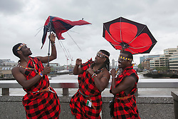 © licensed to London News Pictures. London, UK 01/01/2000. Isaac Stephen, Abrajah Rafiq and Lloyd Benson posing with umbrellas after handing out tea gift packages from Kenya to London commuters to celebrate Queen?s Diamond Jubilee this morning on London Bridge. Photo credit: Tolga Akmen/LNP