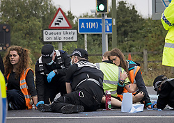 © Licensed to London News Pictures. 20/09/2021. Welwyn Garden City, UK. Protesters embrace while having their hand removed form the road. Protesters from Insulate Britain attempt to blockade the A1M junction 4 near Welwyn Garden City, Hertfordshire. Climate change activists Environmental protest group Insulate Britain have successfully blocked traffic at various points of the M25 on several occasions over the past week. Photo credit: Ben Cawthra/LNP
