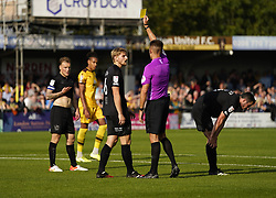 Port Vale's Nathan Smith is shown a yellow card by referee Declan Bourne during the Sky Bet League Two match at Borough Sports Ground, Sutton. Picture date: Saturday October 9, 2021.