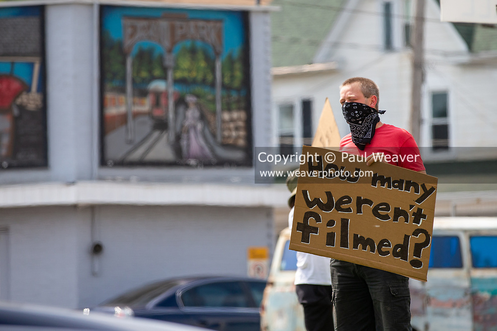 """A protester holds a sign reading """"how many weren't filmed?"""" at a protest in Shamokin, PA on June 4, 2020. About 30 people gathered at Market and Independence Streets to protest police violence and racism."""