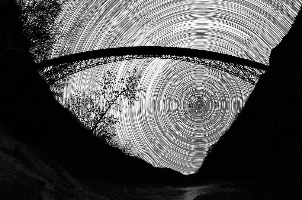 The movement of the stars hang frozen in the sky, the same ancient beams of light that saw the formation of the New River Gorge itself now contour it's shape as if to hold the giant steel arch bridge delicately above the ravine.