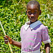 A Kenyan schoolgirl snacking on sugarcane, which grows in abundance in Nandi County, Rift Valley Province.