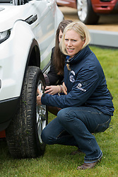 © London News Pictures. 08/05/2012. Windsor, UK.  Zara Phillips changing a tyre as she talks to safety engineer graduate Verity Atkins from Land Rover at the launch of the Range Rover Evoque Scholarship on Day one of the Royal Windsor Horse Show, set in the grounds of Windsor Castle.  Photo credit: Ben Cawthra/LNP