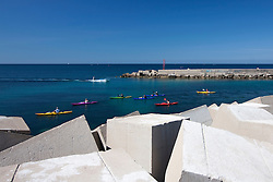 Gruppo di persone in canoa si sofferma a guardare una barca a motore che entra nel porto di Gallipoli (LE)