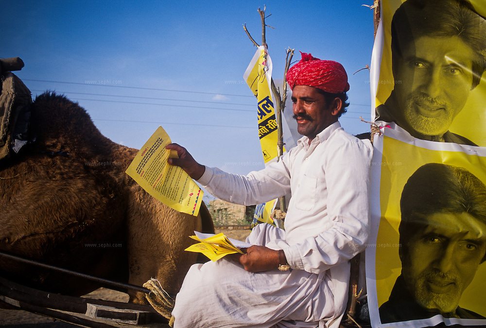 A Rajasthani musician on a camel cart adorned with posters of Amitabh Bachchan, India's most famous movie star. Singers and musicians like these help motivate health workers and convince parents to have their children immunized.<br /> This 'social mobilization' draws on the entire society to promote polio eradication.