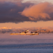 website: www.aziznasutiphotography.com                                        This picture has been taken in -15 degree in Trondheim. It was fabulous with the sun and the moody clouds. A frozen part of the smoky waters.