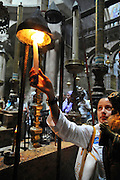 Israel, Jerusalem Old City, the Church of the Holy Sepulchre pilgrims light candles near the Rotunda