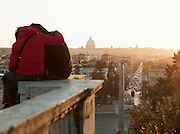 Couple sat on wall overlooking Piazza Del Popolo, Rome, Italy.