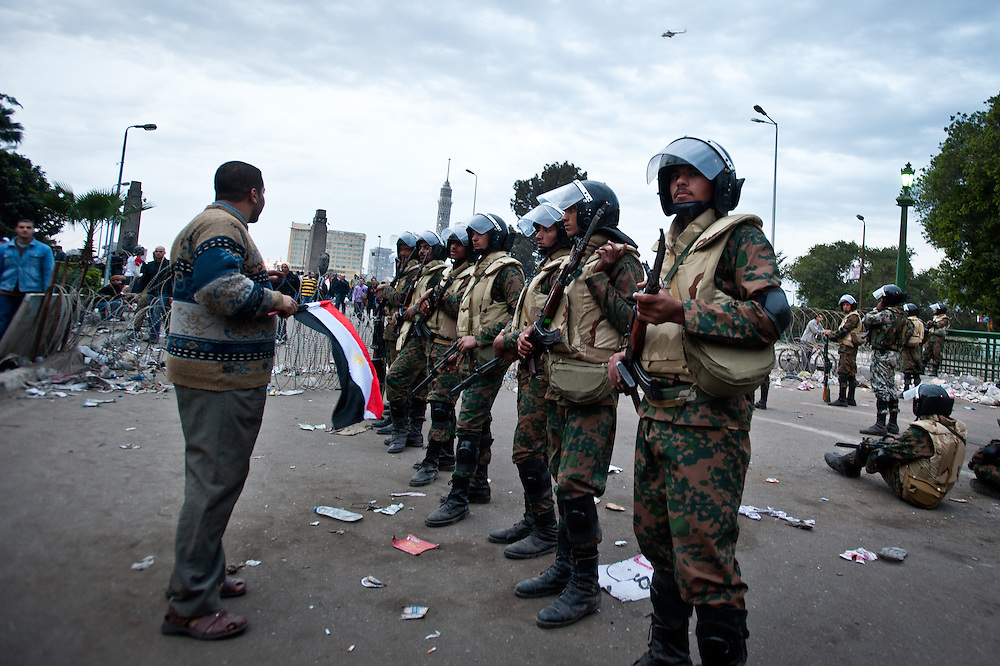 An anti-government protester carrying an Egyptian flag talks with soldiers from the Egyptian army at the beginning of the Kasr-el-Nil Bridge. Thus far in the Egyptian crisis, the army has been perceived as a mediator, and even made an official statement that they would not fire on civilians.