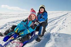 Brother and sister sledging down hill, smiling, Bavaria, Germany