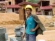 An Akha man from a nearby village working on the construction of the new village of Ban Sam Sang, Phongsaly province, Lao PDR. Four Laoseng ethnic minority villages will be relocated permanently to this new village before the end of 2015 due to the construction of the Nam Ou Cascade Hydropower Project Dam 6.
