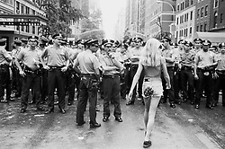 Young blonde woman in short shorts walking toward a crowd of police officers in New York City