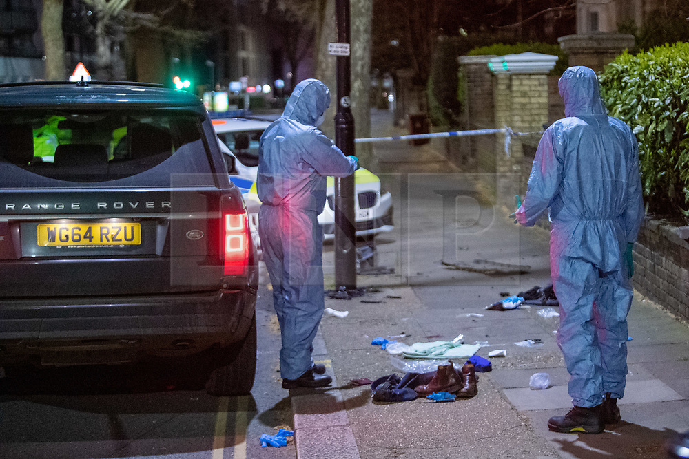 **Incident reported to be connected with the death of Multi-millionaire hotelier Sir Richard Sutton in Dorset**<br /> © Licensed to London News Pictures. 08/04/2021. London, UK. Forensic investigators survey the scene standing next to a knife, jeans and shoes on Chiswick High Road following a incident in which a vehicle was stopped by armed police at approximately 22:30hrs on Wednesday 07/04/2021 when police approached the vehicle, officers discovered the lone male occupant had sustained a number of serious self-inflicted injuries. First aid was commenced immediately and the London Ambulance Service were called. The male has been taken to a west London hospital. Photo credit: Peter Manning/LNP