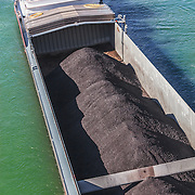 A cargo boat transporting asphalt for paving and construction on the Rhein river in Basel, Switzerland.<br /> <br /> LICENSING: This image can only be licensed through SpacesImages. Click on the link below:<br /> <br /> http://tinyurl.com/cpb4ckt