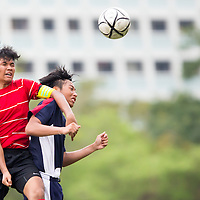 Muhammad Nabil (#16) heads the ball against Lionel Chua (#18) of Yishun Junior College during the group stage match of the National 'A' Division Football Championship at Meridian Junior College on April 1, 2014, in Singapore.