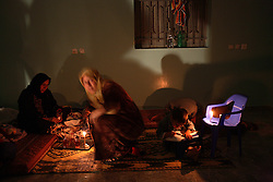 Subhia Al-Athamneh, 52, and relatives sit by candle light in their home, which was damaged after Israeli airstrikes targeting a neighbor went astray, Beit Hanoun, Gaza Strip, Palestinian Territories, Nov. 16, 2006. According to Human Rights Watch, since September 2005, Israel has fired about 15,000 rounds at Gaza while Palestinian militants have fired around 1,700 back.