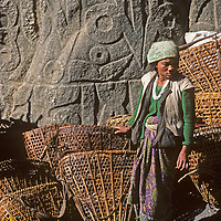 A young lowland Hindu woman rests after carrying a basketful of goods to the weekly Saturday market in Namche Bazaar, the leading Sherpa town of Nepal's Himalaya.  Behind her is a huge mani stone carved with Tibetan Buddhist prayers.