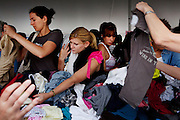BETHLEHEM, PA – JUNE 11, 2011: Mounds of clothing grow on tables as items are tossed back and forth between shoppers during the first hour of the sale.<br /> <br /> As the population of second and third generation Hispanics increases dramatically in the United States, a new boldness can be sensed among Latinos in America, stretching far beyond the southern border states. Demographers in Pennsylvania say the towns of Bethlehem, Allentown and Reading are set to become majority-minority cities, where Hispanics comprise a bigger portion of the population than whites. As this minority population increases dramatically in the region, Latinos are inching closer to their own realization of the American Dream, while gradually shifting the physical and cultural landscapes of their communities.