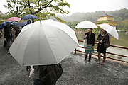tourist on a rainy day with the Kinkakuji temple in Kyoto in the background