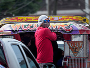 """30 JANUARY 2018 - GUINOBATAN, ALBAY, PHILIPPINES: A ticket taker on the back of a """"Jeepney"""" with a face mask and his head covered during an ash fall. Mayon volcano continued to erupt but not as dramatically as it did last week. The small eruptions are still sending ash clouds over communities west of the volcano and the government is encouraging people to stay indoors, wear face masks and avoid strenuous activities when ash is falling.     PHOTO BY JACK KURTZ"""
