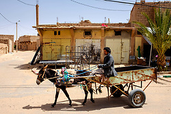 A man drives a donkey and cart along a street  in Mhamid, Morocco<br /> <br /> (c) Andrew Wilson | Edinburgh Elite media
