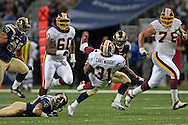 Washington Redskins running back Rock Cartwright (C) gets tripped by St. Louis Rams safety Mike Furrey (L) after a 25-yard gain in the second quarter, during the Redskins 24-9 win at the Edward Jones Dome in St. Louis, Missouri, December 4, 2005.