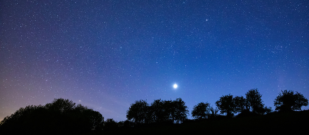 Multitude of stars and a shooting star in night sky with Venus at its brightest stage this year in prominent view over southern England, United Kingdom